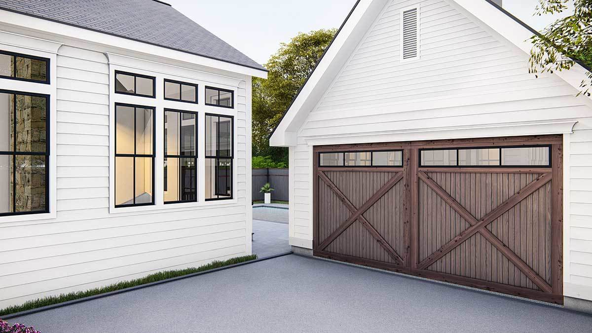 A closer look at the detached garage with white siding and barn style garage doors.