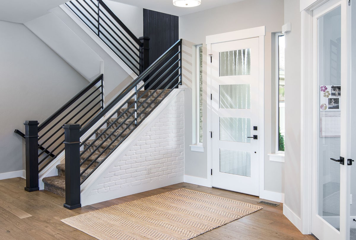 A carpeted staircase with wrought iron railings welcomes you upon entry.