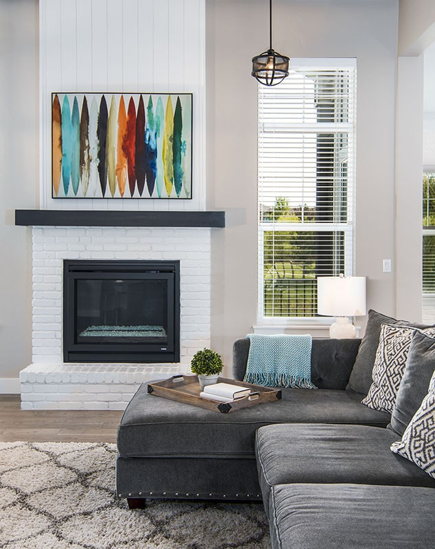 A close-up look at the brick fireplace adorned by an abstract painting.