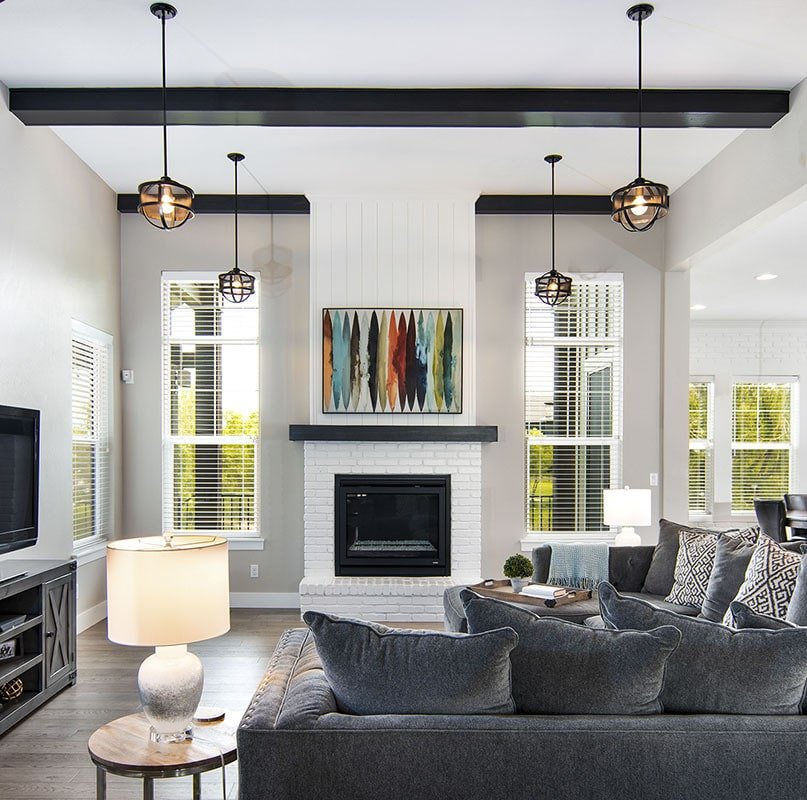 The living room has a fireplace, an L-shaped sofa, and wooden tables.
