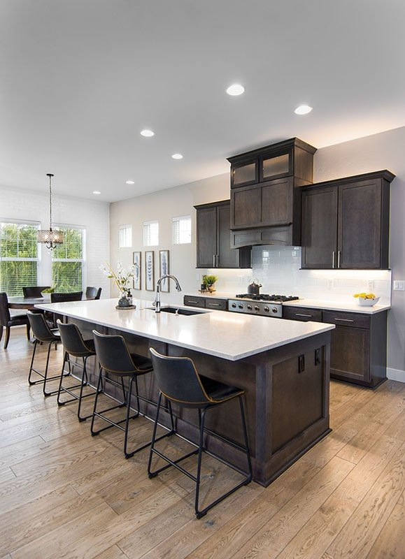 The kitchen offers dark wood cabinetry, white subway tile backsplash, and a large breakfast island fitted with a sink.