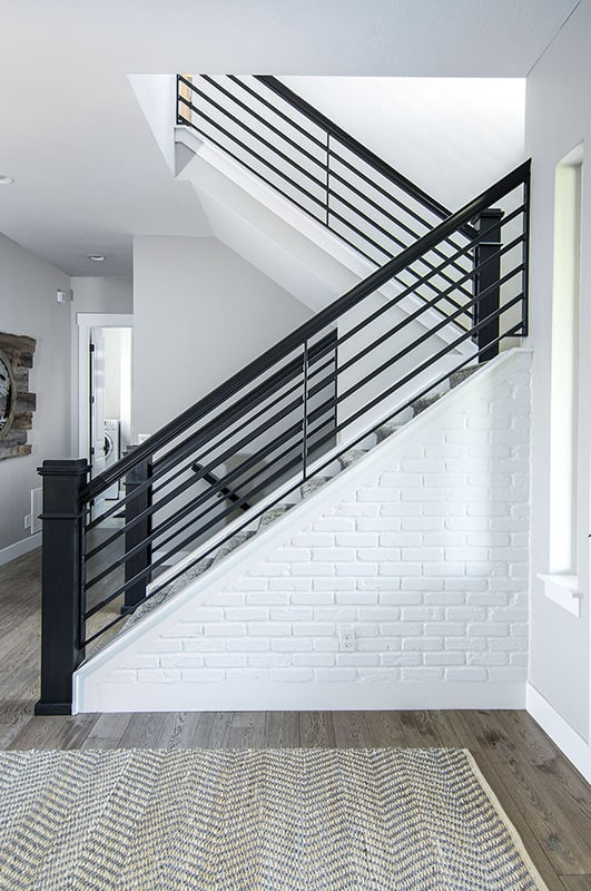 Staircase with wrought iron railings leading to the bedroom upstairs.