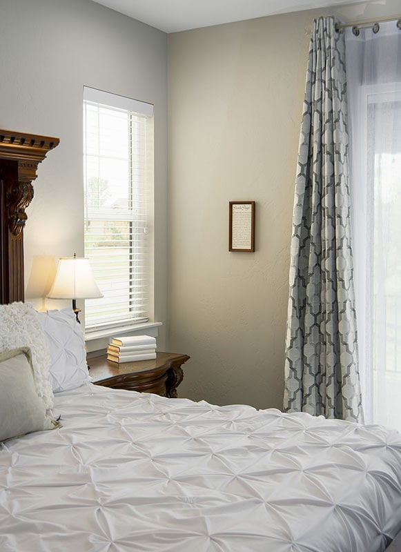 The primary bedroom has beige walls and a cozy wooden bed dressed in a deluxe white quilt.
