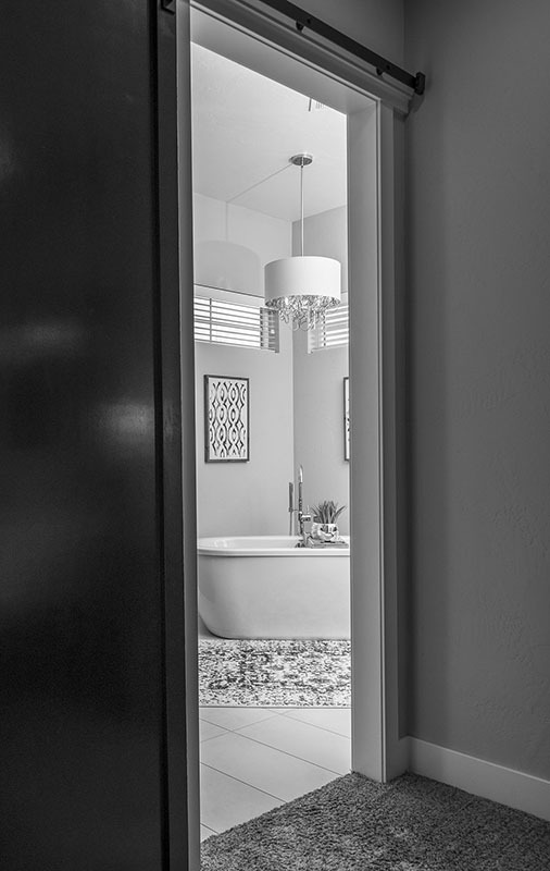A sliding barn door opens to the primary bathroom.
