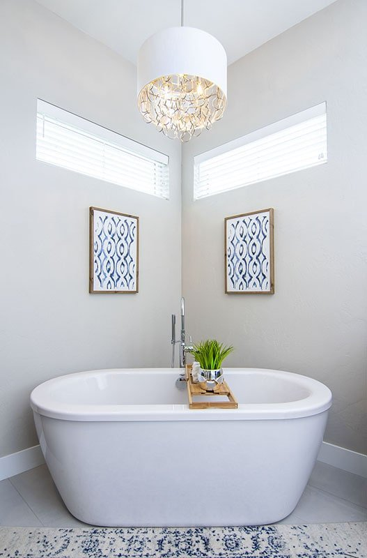 A fancy drum chandelier illuminates the freestanding tub.