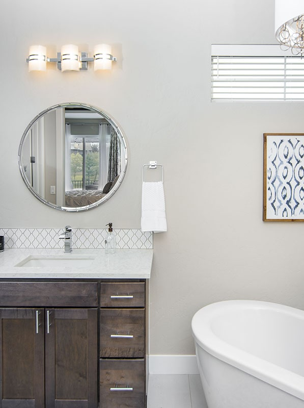 The sink vanity is paired with a round mirror and warm glass sconces.
