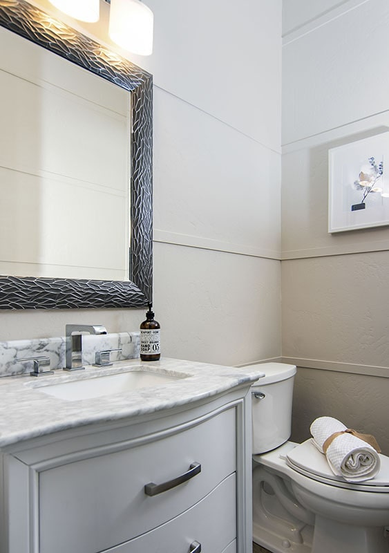 Powder bath with a marble top vanity and a toilet.