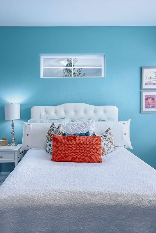 This bedroom has white furnishings and blue walls graced with framed artworks.