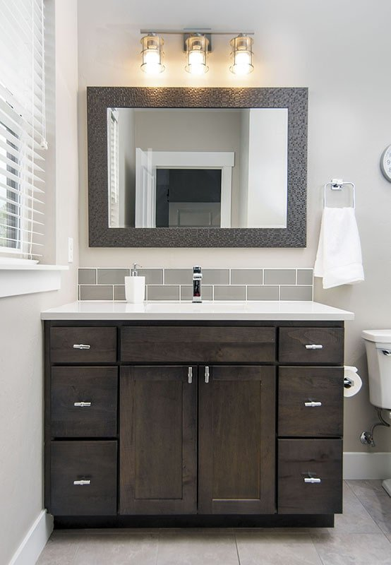 Sink vanity with dark wood cabinets and a large framed mirror.