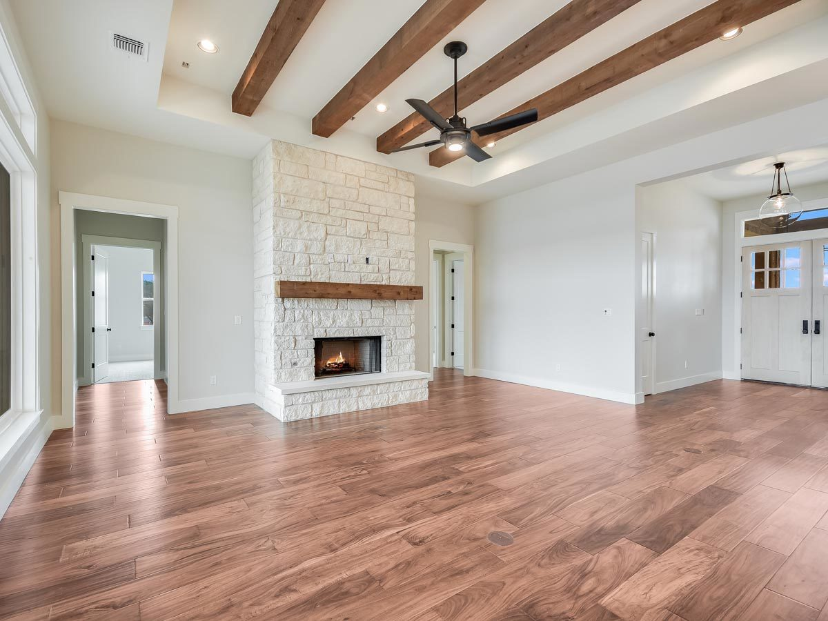 The living room has a stone fireplace and a beamed ceiling.