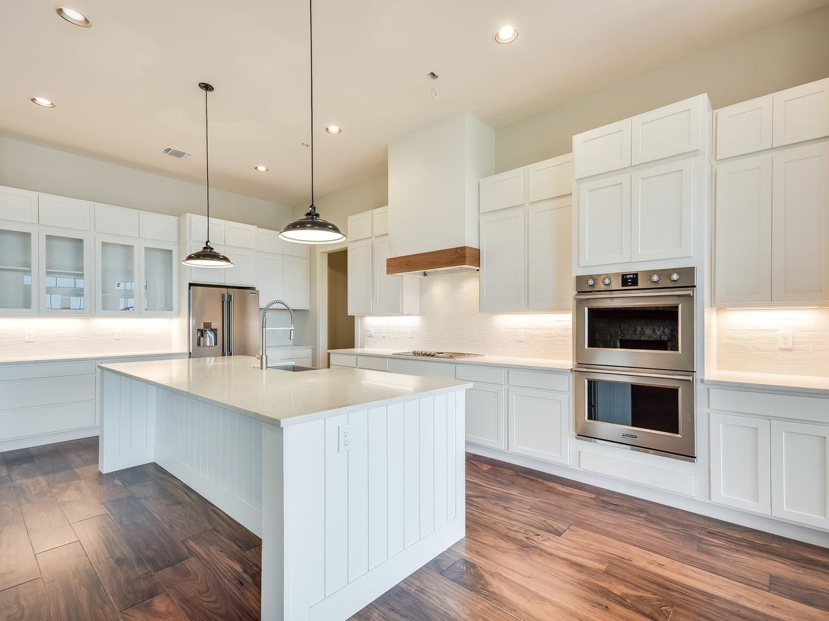 The kitchen is equipped with stainless steel appliances, white cabinetry, marble countertops, and a center island.