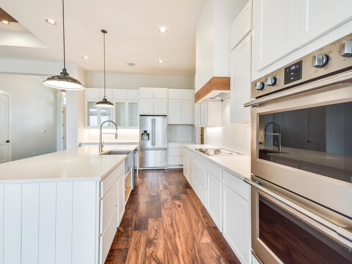 The beautiful hardwood flooring creates a stunning contrast to the white cabinetry.