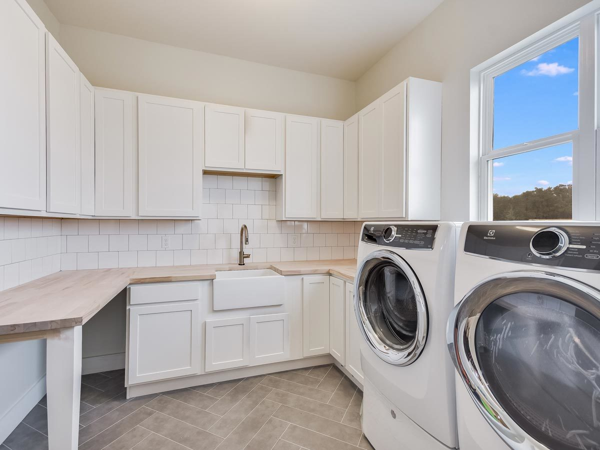 Laundry room with white front-load appliances, wooden countertop, white cabinets, and a farmhouse sink.