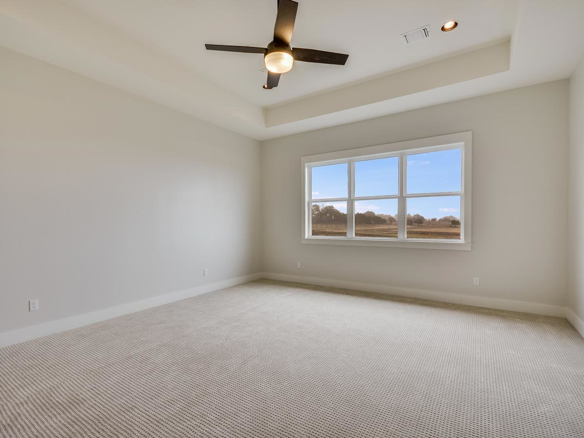 Primary bedroom with beige walls, carpet flooring, white-framed windows, and a tray ceiling mounted with a ceiling fan.