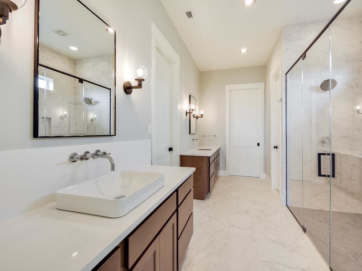 The primary bathroom offers his and her vanities, a toilet room, and a large walk-in shower.