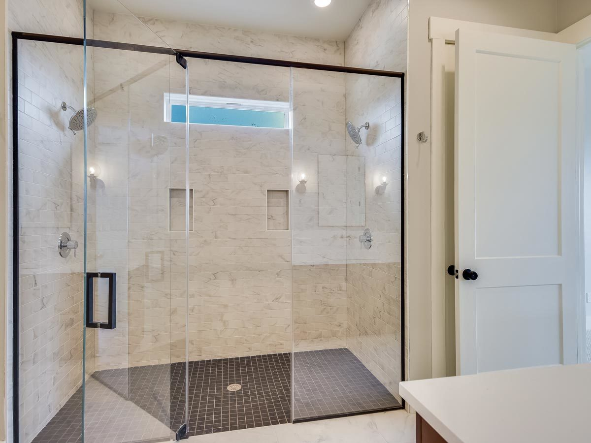 The walk-in shower features two shower heads, tiled walls, chrome fixtures, and inset shelves.