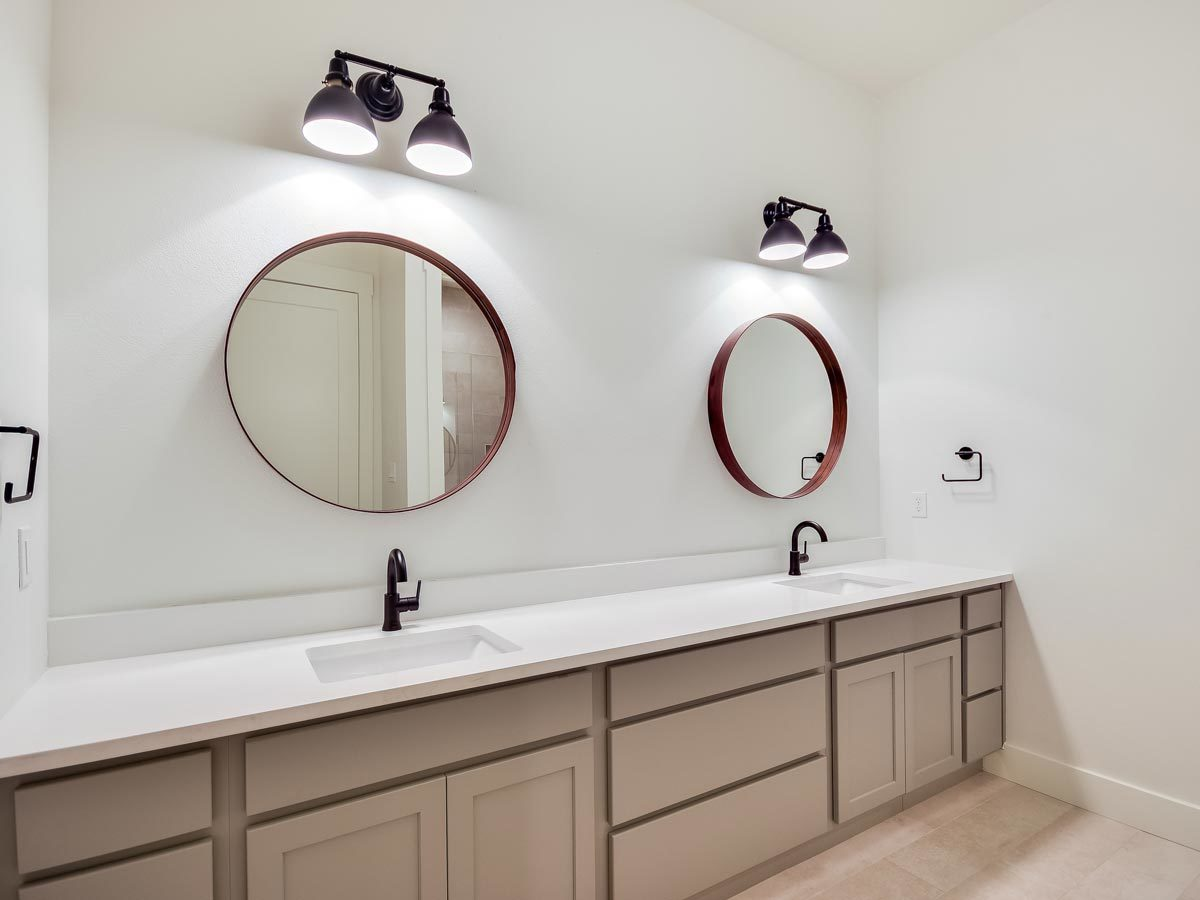 A double sink vanity with wrought iron fixtures, round mirrors, and wall sconces.
