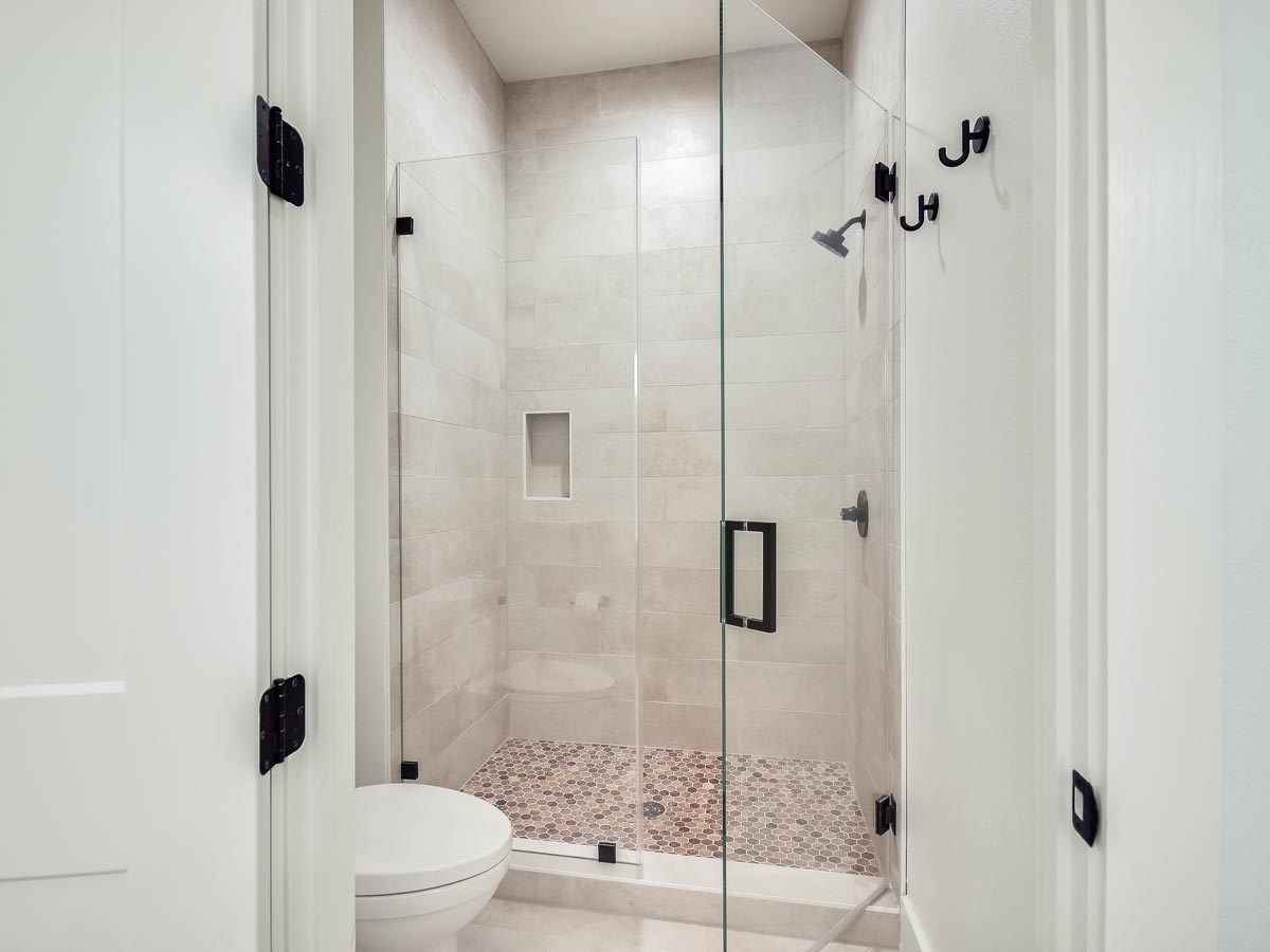 This bathroom has a toilet and a walk-in shower enclosed in a hinged glass door.