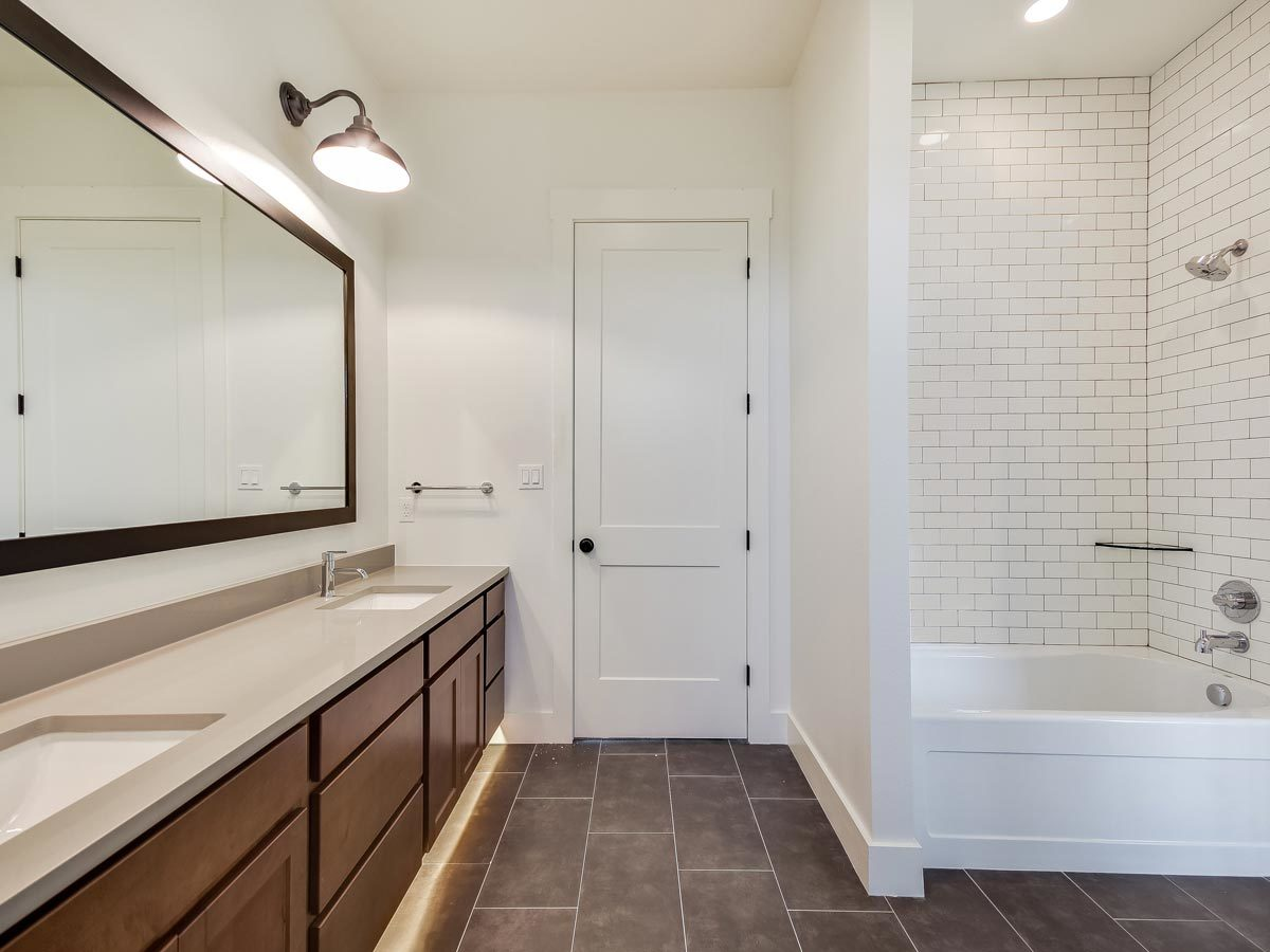 Another bathroom with a tub and shower combo and a dual sink vanity paired with a large rectangular mirror.