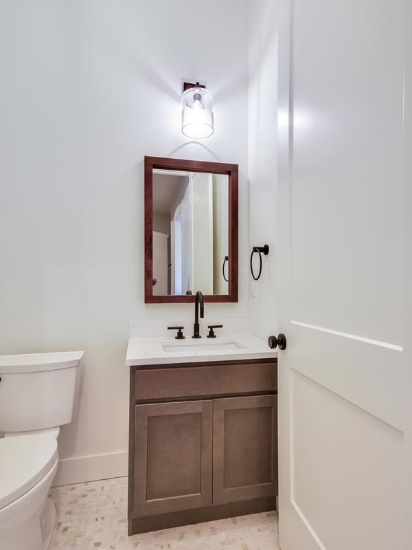 Powder room with a toilet and a wooden vanity.