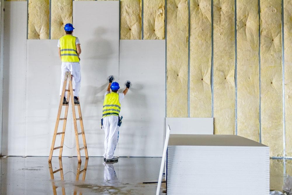 Workers installing plasterboards.