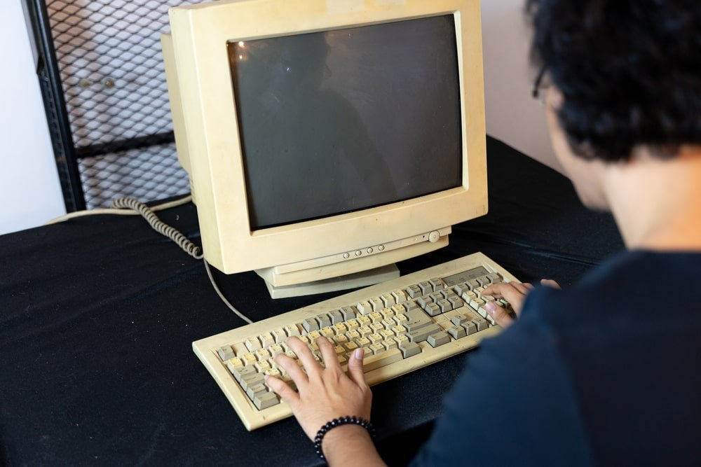 A man using an old personal computer.