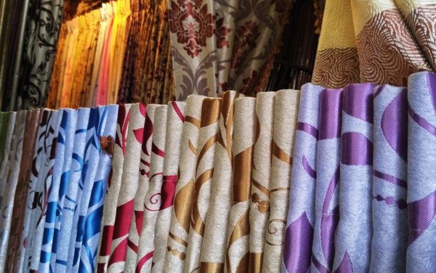 A close look at various curtains on display at a store.