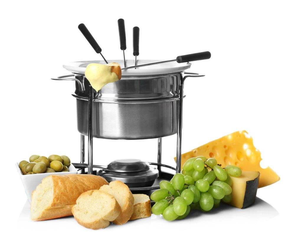 Stainless steel fondue pot with bread, grapes, and cheese.