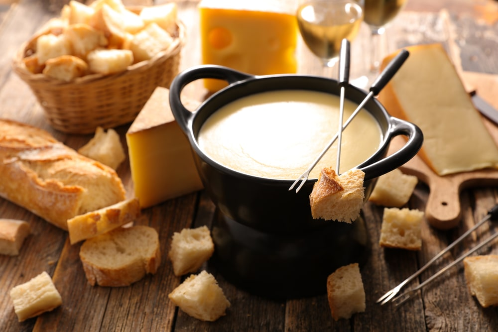 Cast iron fondue pot filled with cheese.