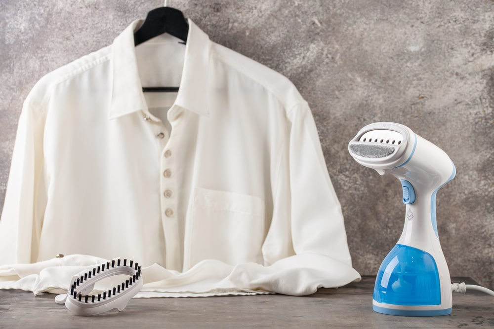 White blouse on a hanger with a portable iron on the side.