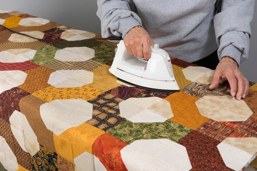 A man ironing a bow tie quilt.