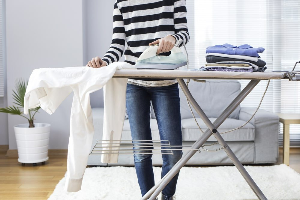 Man ironing a polo on ironing board.