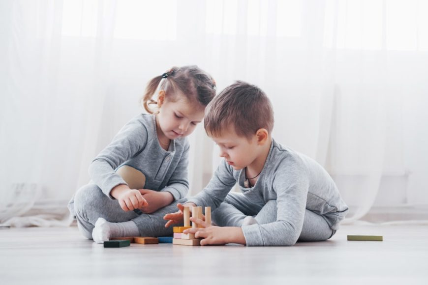 Two kids playing with blocks and toys on the floor.