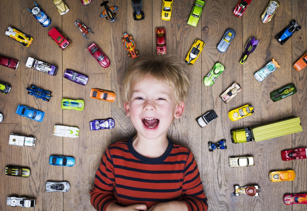 A boy surrounded by multiple toy cars.