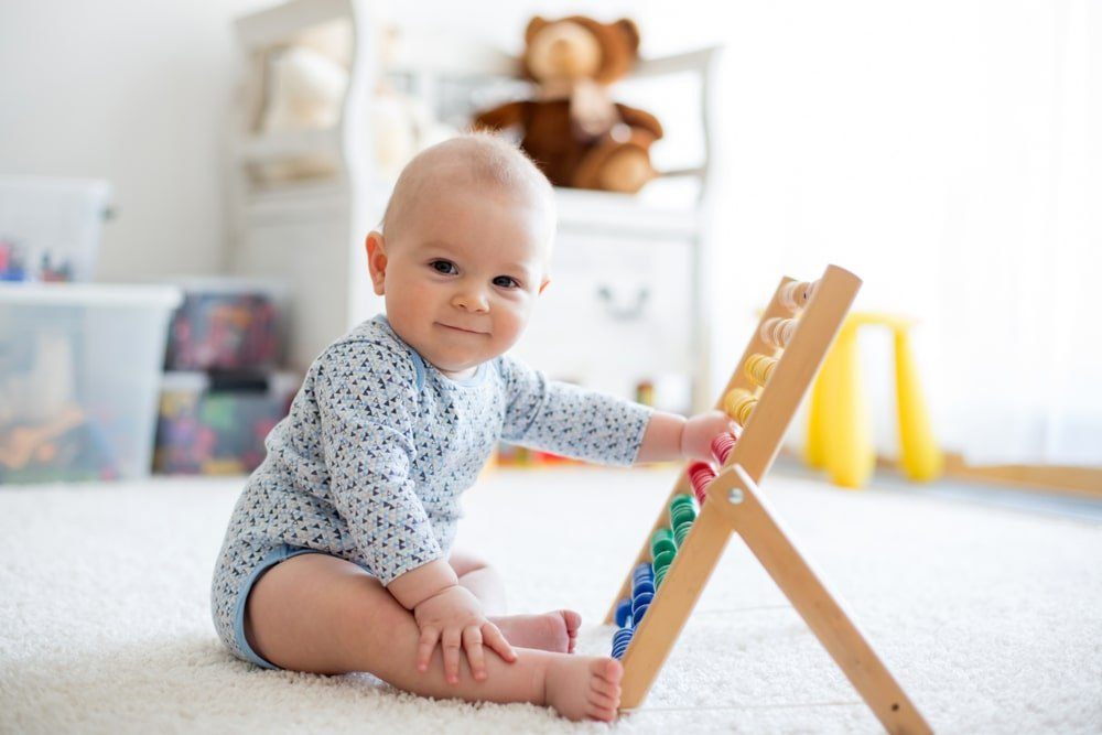 A baby playing with a colorful wooden toy.