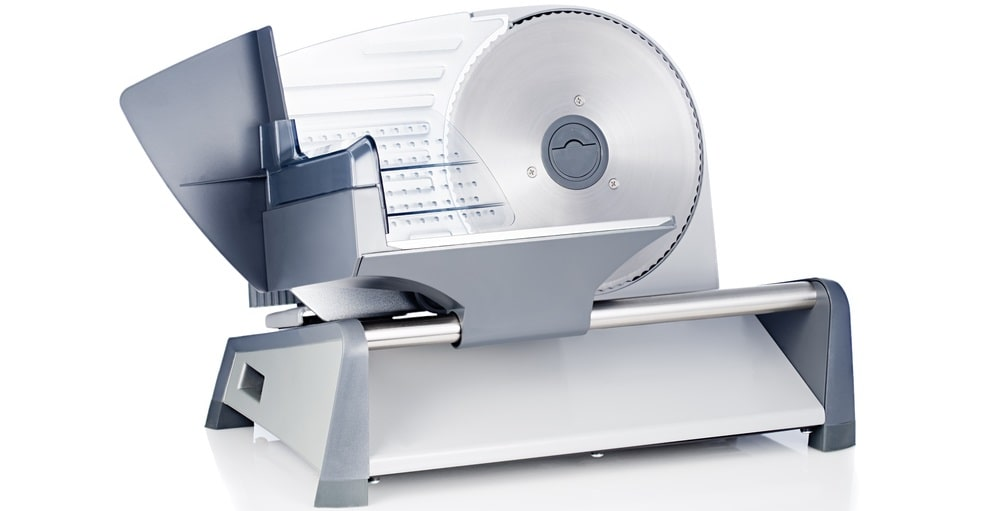 A stainless steel manual meat slicer against a white background.
