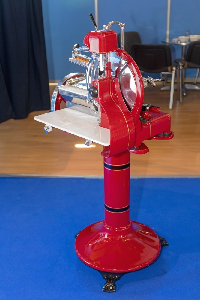 A red vintage meat cutter with flywheel.