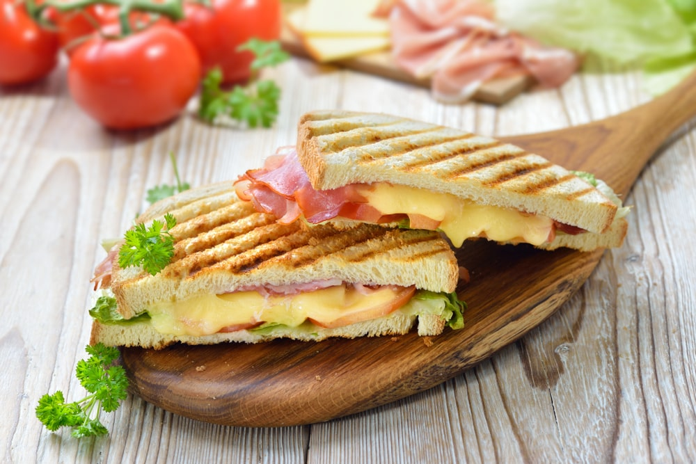 Grilled and pressed toast with smoked ham, cheese, tomato and lettuce served on wooden cutting board.
