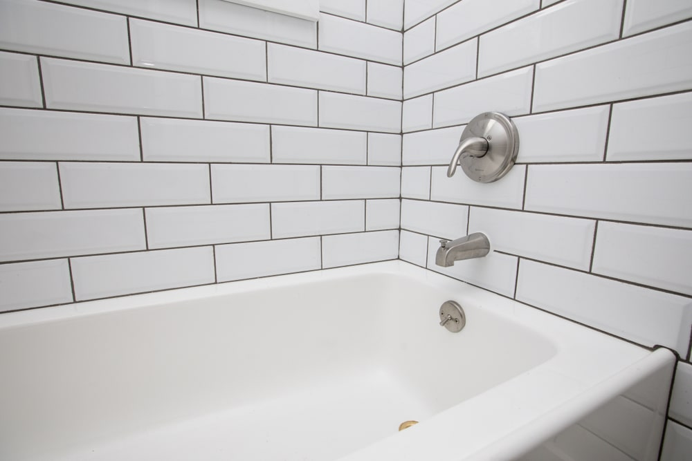 Closeup of bathtub with chrome fixtures fitted on tiled walls.