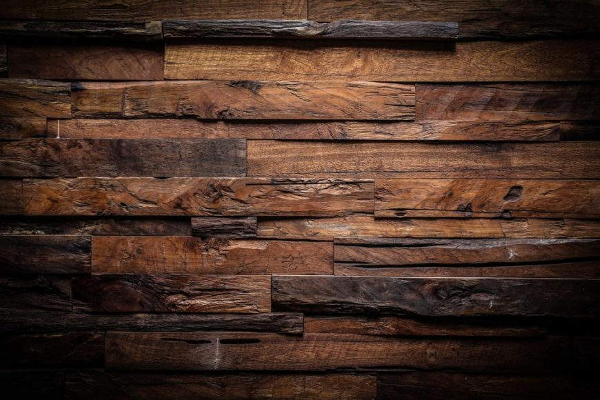 A close look at a dark textured wall made of various wood of different grain patterns.