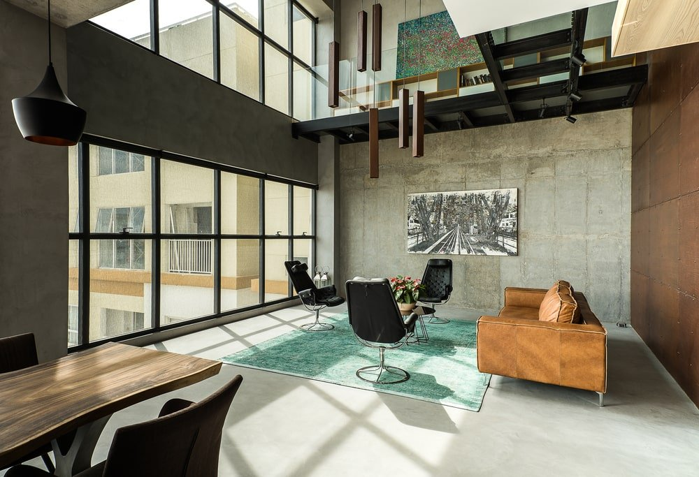 This is a full view of the living room that has a large brown leather sofa across from the large glass wall that brings in natural lighting.