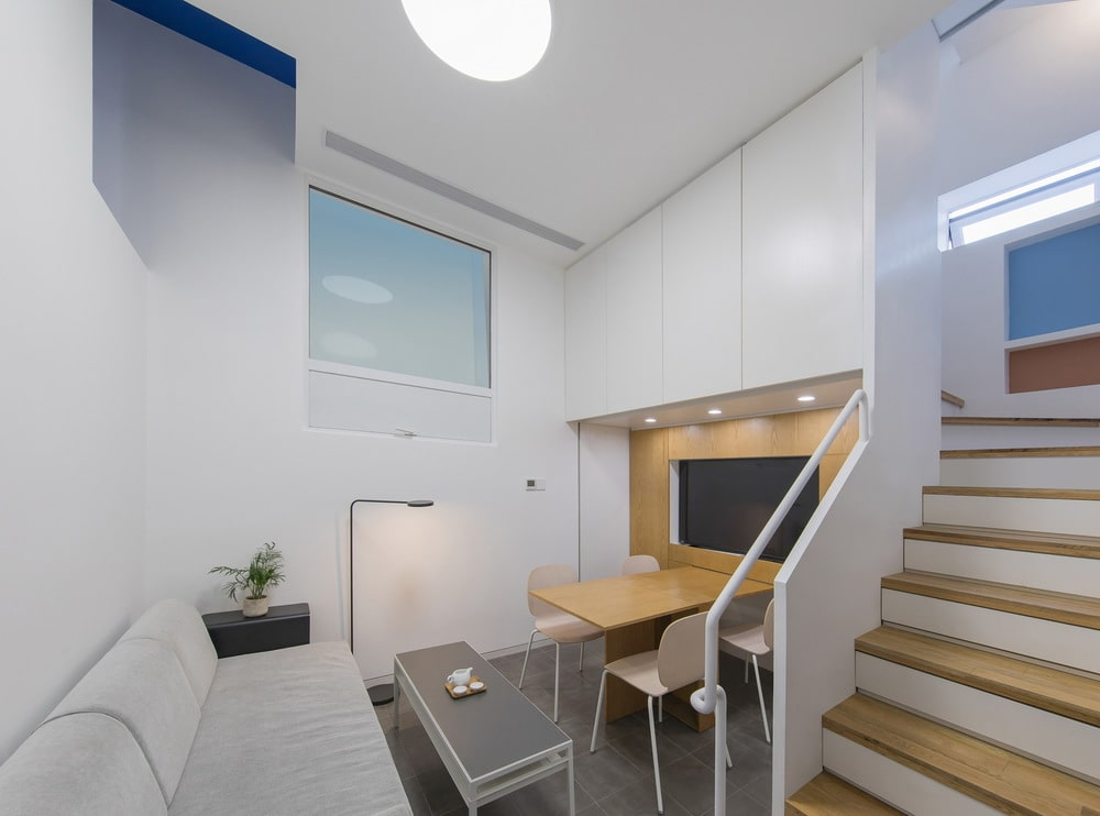 After the sofa of the living room area is the dining area that has a built-in wooden table with a wall-mounted TV above.