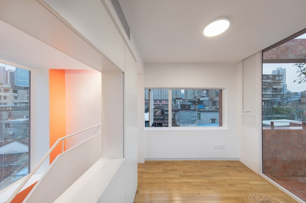 This is a the top floor landing with hardwood flooring, white walls and glass windows.