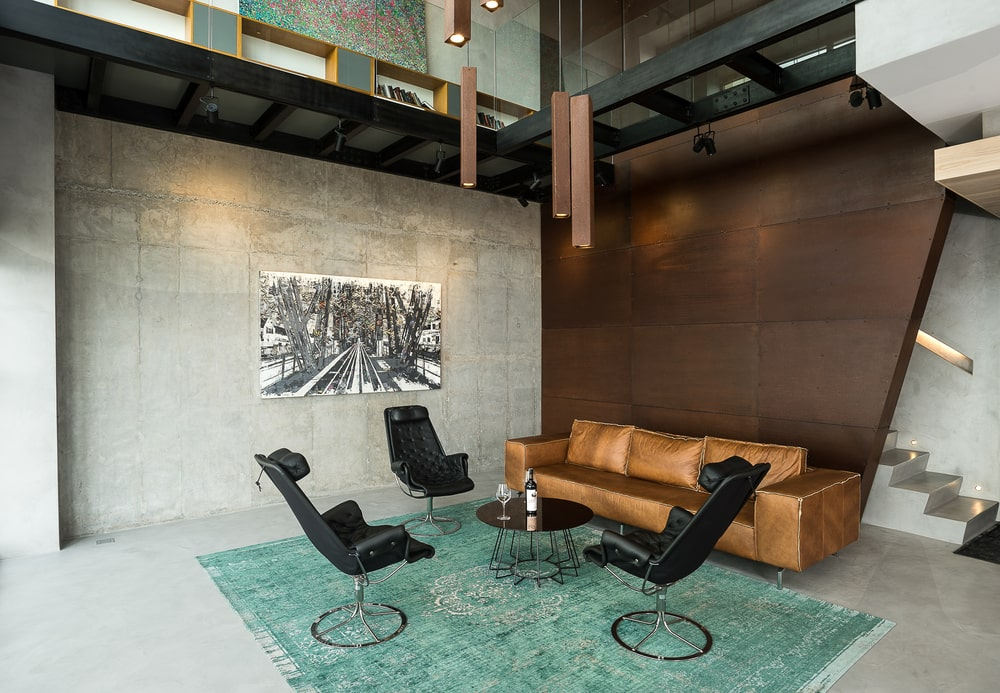 The black coffee table matches well with the three black leather chairs that stand out against the blue area rug.