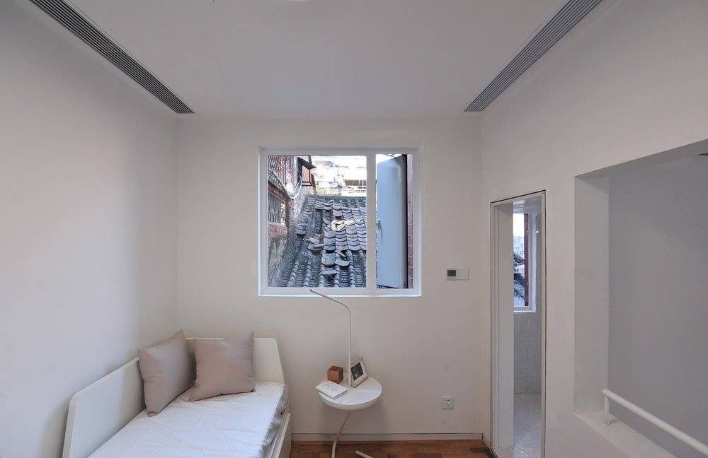 This small room has a white cushioned platform bed at the corner by the window with a small side table.