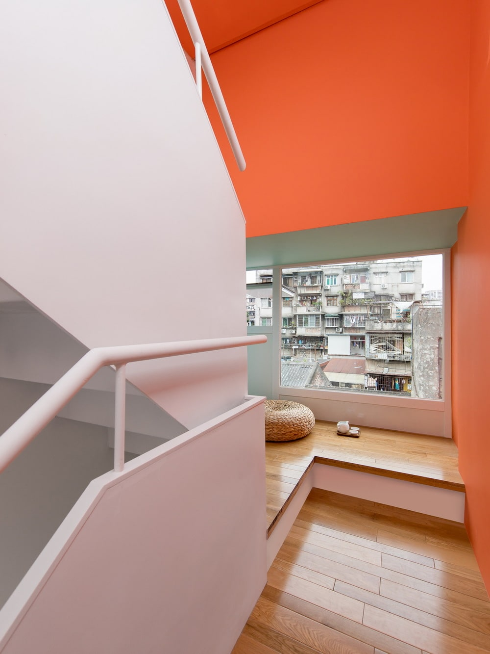 This is a close look at a stairs landing with a reading nook by the window.