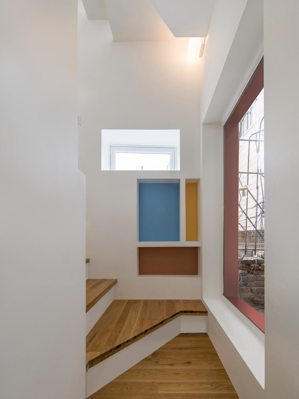 This is a close look at the staircase with wooden steps and a large window on the side.