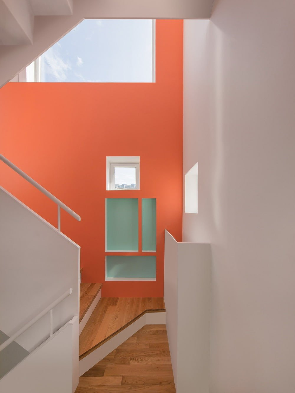 This is a look at the staircase painted with a bright salmon color that pairs well with the white staircase.