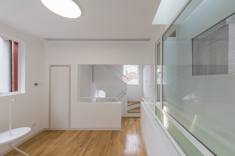 This is the other view of the bedroom that has white walls and ceiling as well as a glass wall brightened by the windows.
