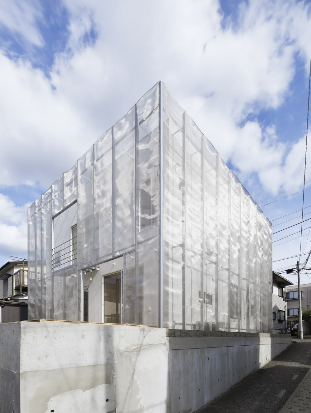 This is a full view of the house that has a unique look to it thanks to the see-thru screen-like material on the outer wall of the house.